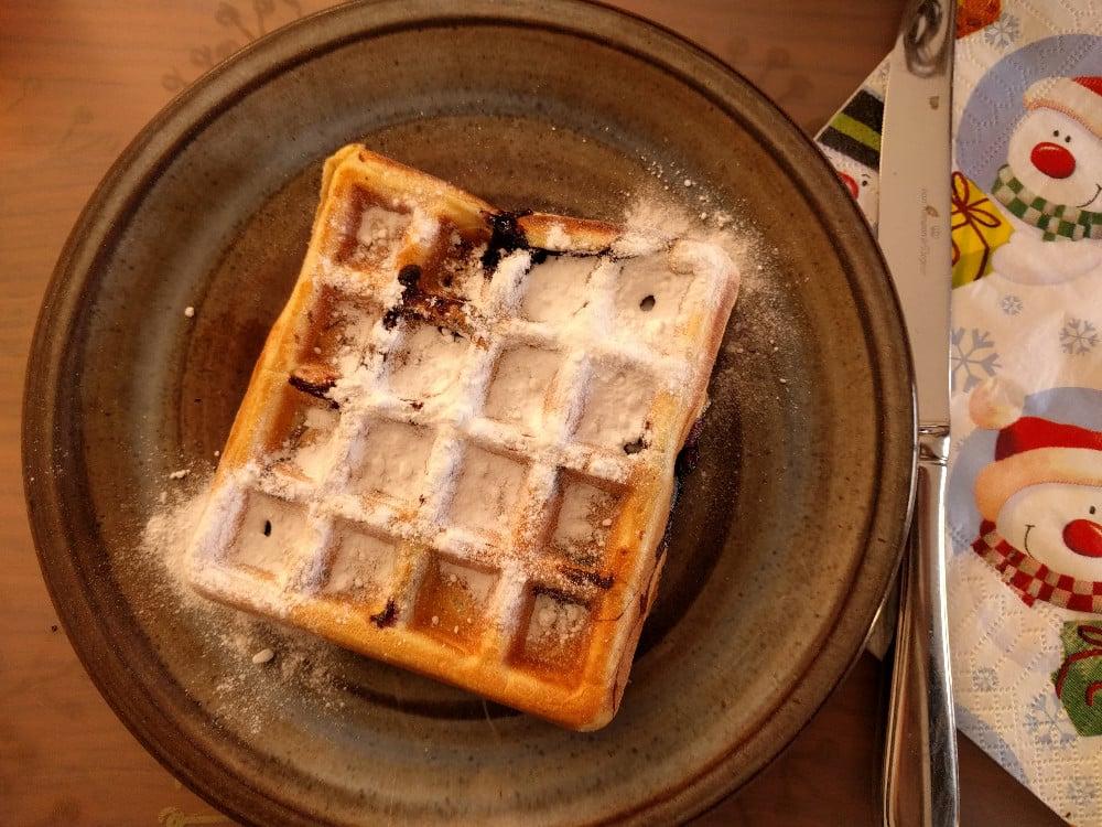 freshly baked waffle with icing sugar