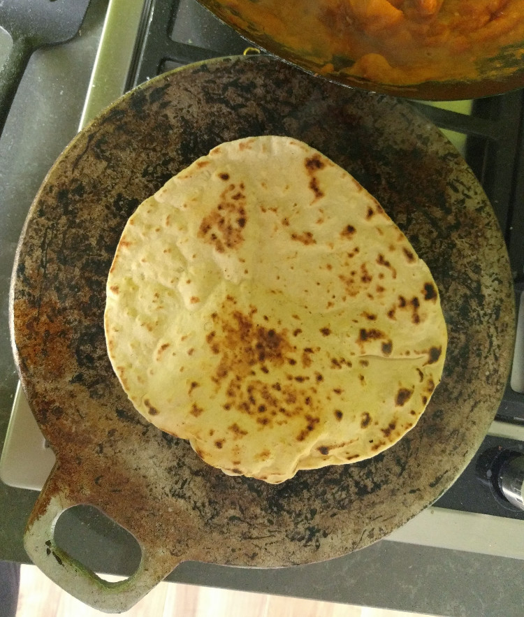 baking naan on a flat tawa