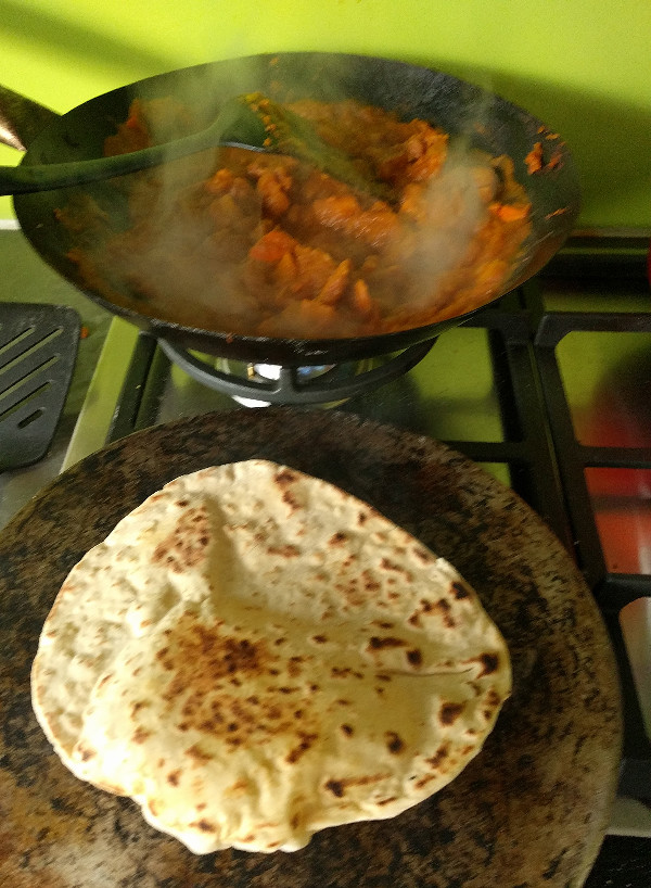 baking naan on a tawa with butter chicken