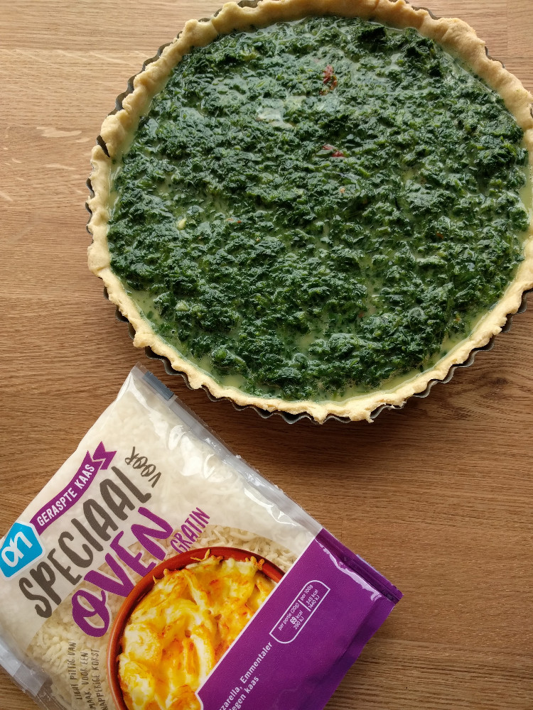 spinach quiche ready for covering with cheese mix