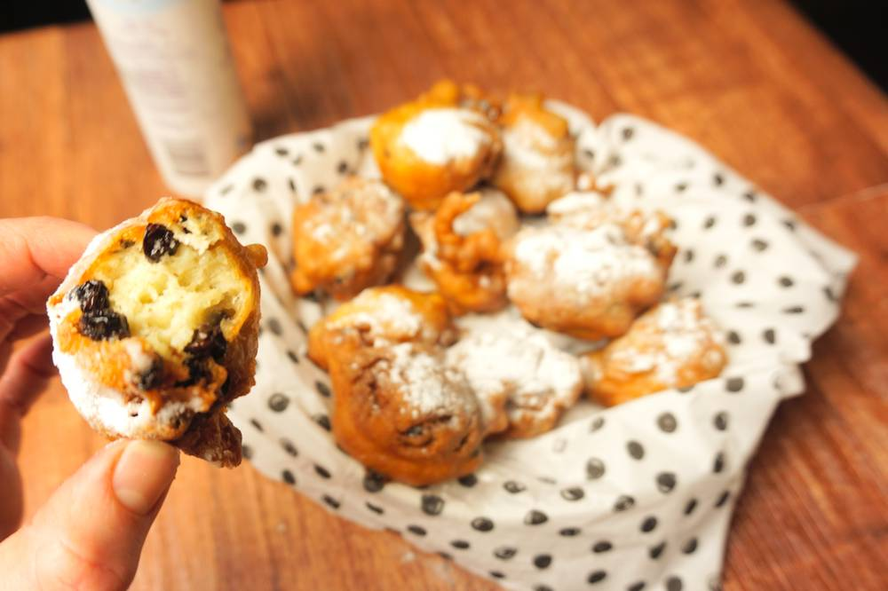 oliebollen - dutch donuts - with and without raisins and with icing sugar, one with bite